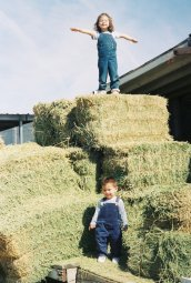 Amina and Adam playing on the hay